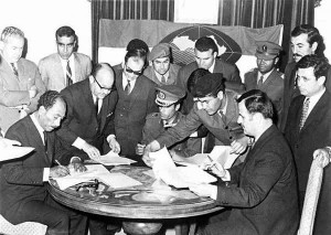 Assad signing the Federation of Arab Republics in Benghazi, Libya, on 18 April 1971 with President Anwar al-Sadat (sitting left) of Egypt and Colonel Muammar al-Qaddafi of Libya (sitting in the centre).